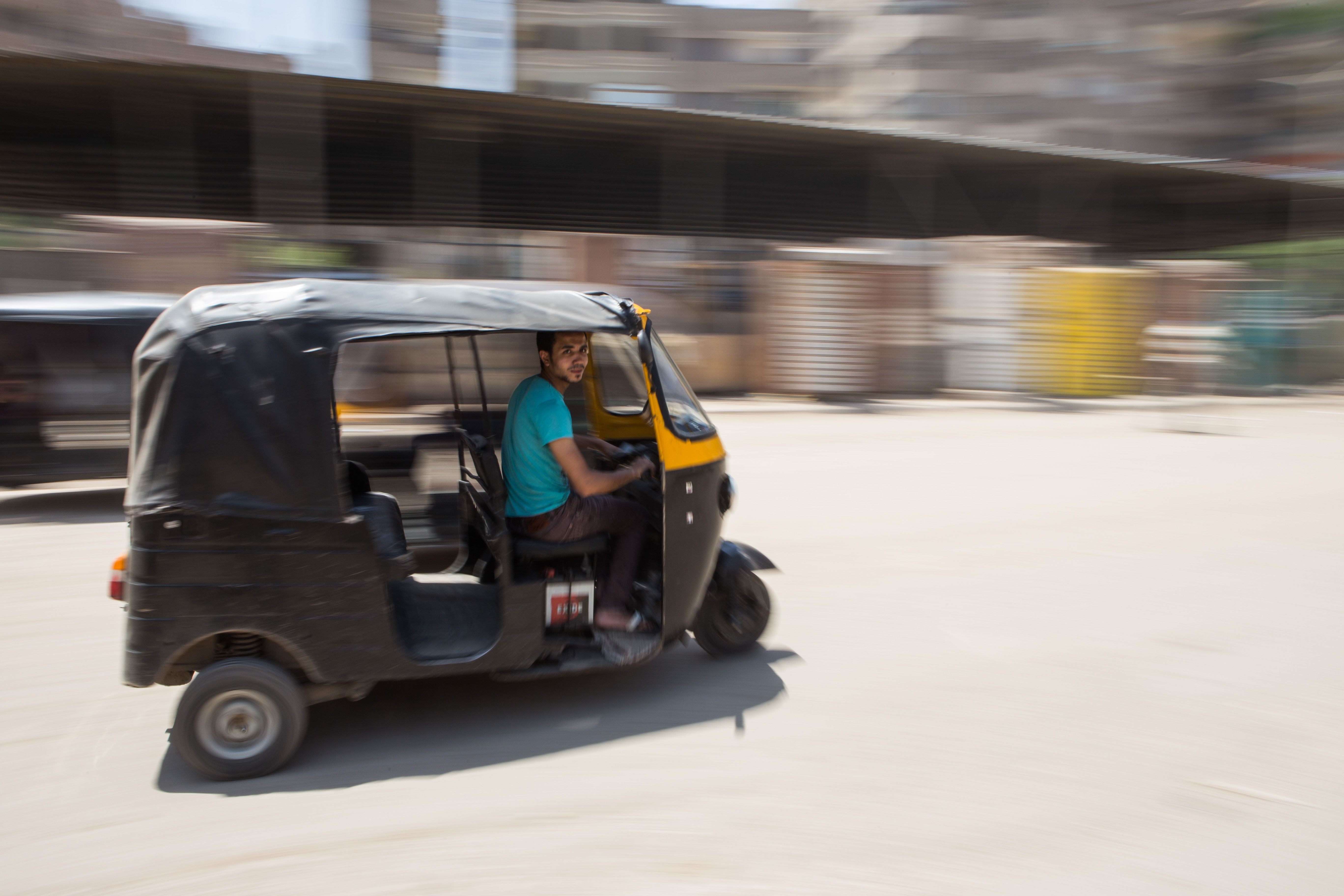 A tuk tuk driver whizzes through the streets of Mohandiseen, Cairo. May 1, 2014