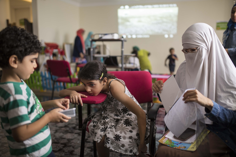 الأم دعاء، والابنة سلمى يتابعان البوصلة التي صنعها عمر في حصة الجغرافيا في مركز براح.