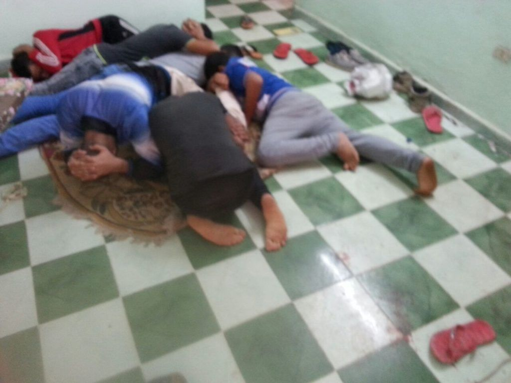 Victim's flatmates simulating the position security officers forced them into during the raid